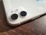 テーブルに置かれた白いiPhone 11のデュアルカメラ周辺